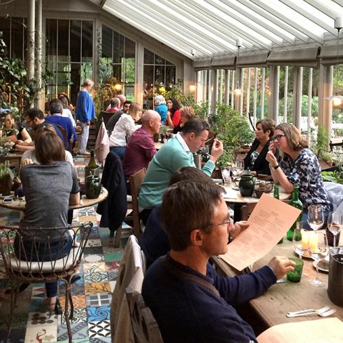 サン・ラウンジ風の空間が広がるレストラン。カラフルなタイルがごちゃ混ぜになっているフロアが見える