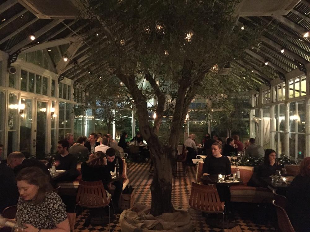 ジーズの内装。水曜日の夜でこの通り満員御礼。19世紀終わりに建てられた温室がレストランに姿を変え、現在に至る